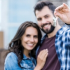 Happy Hispanic couple holding house keys