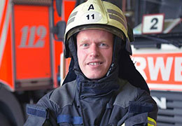 Caucasian firefighter smiling near fire truck